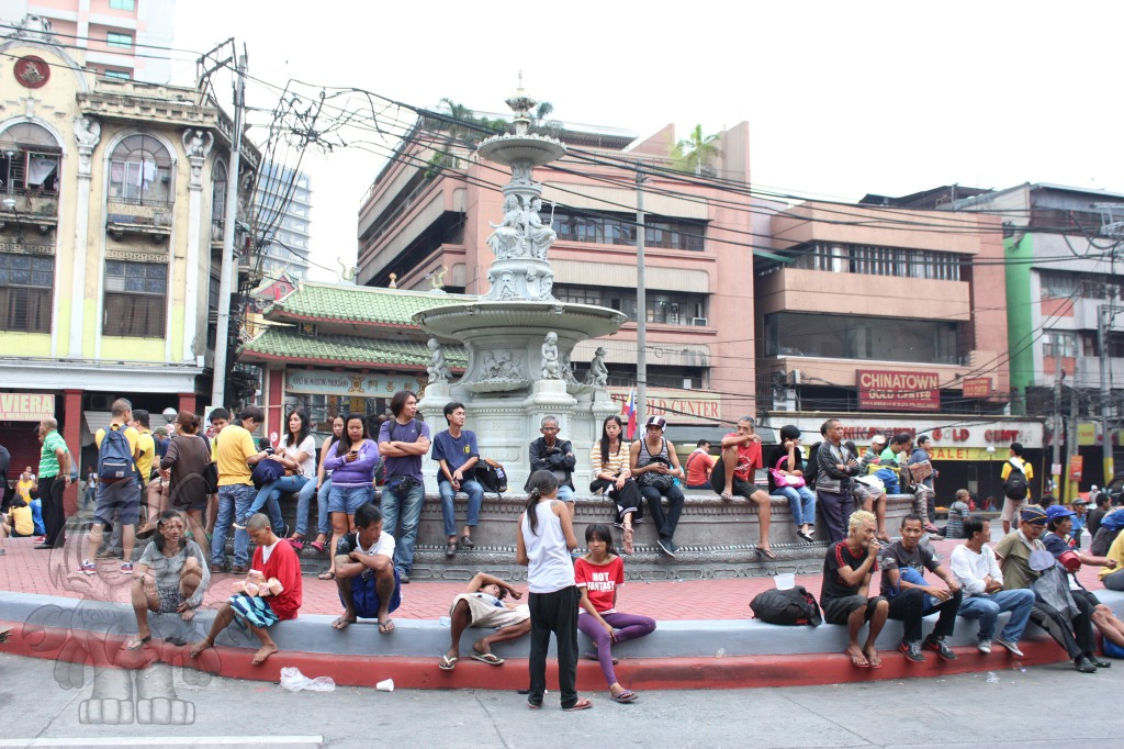 People gathered around the fountain that is in front of the gateway arch of Binondo