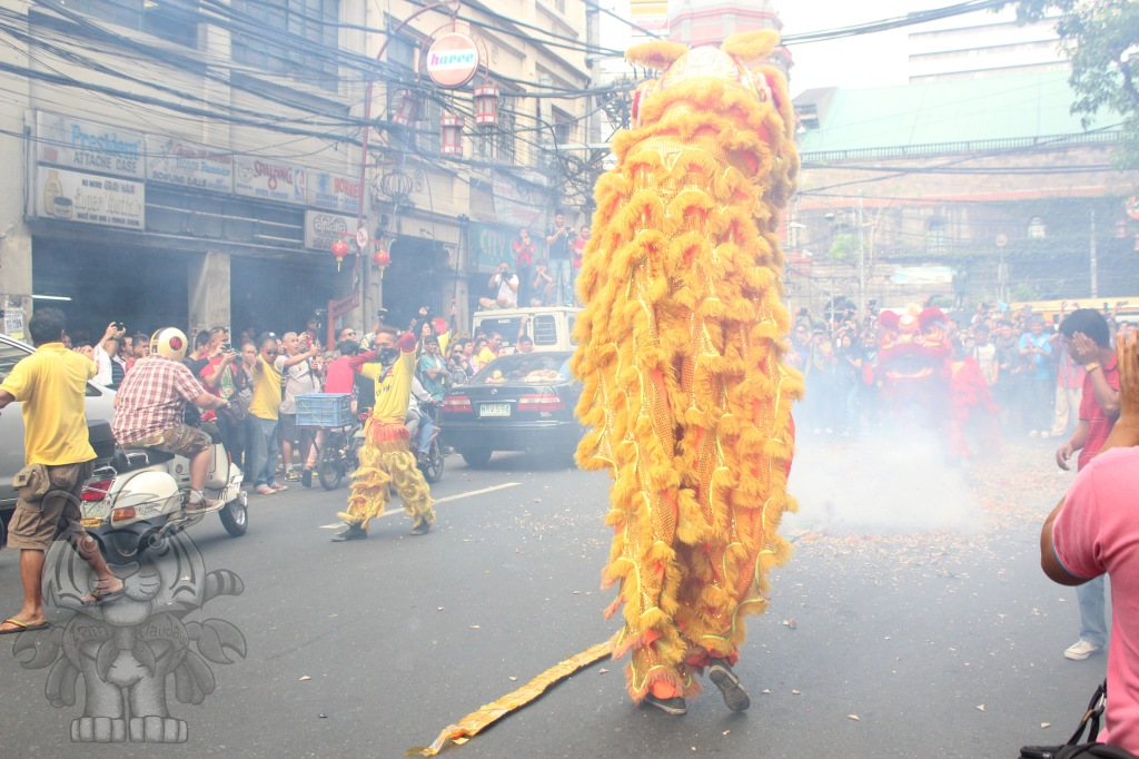 The firecracker pops loudly between two lion dancers