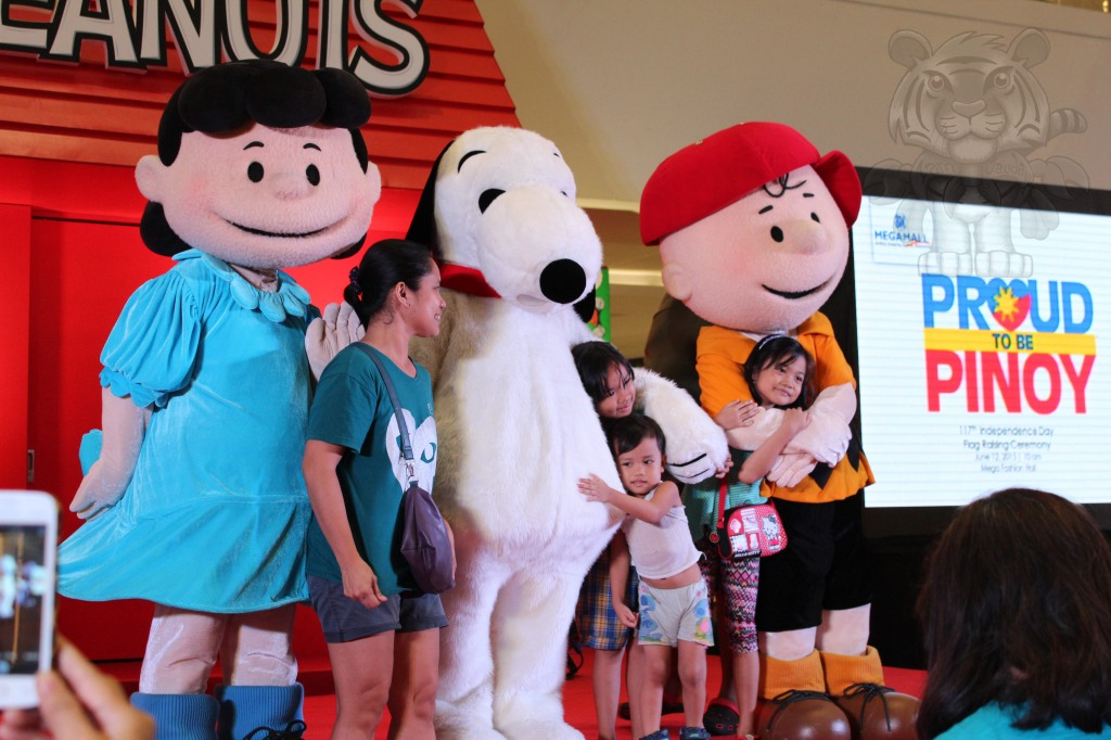 Mascots with families having a picture with them.